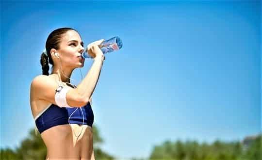 пьет воду девушка бегунья